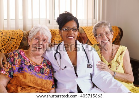 Old people in geriatric hospice: Elderly man and woman hugging an african american doctor, showing a friendly relationship between personnel and patients. - stock photo