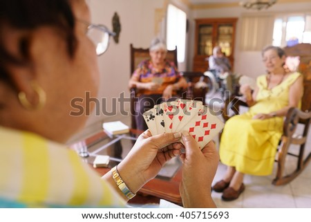Old people in geriatric hospice: group of senior women playing cards and having fun together. The aged ladies sit on the sofa of the hospital and start a new match - stock photo
