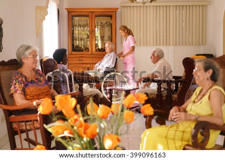 Old people in geriatric hospice: young attractive hispanic woman working as nurse helps a senior man on wheelchair. He joins a group of friends playing chess and having fun - stock photo