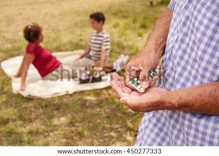 Old people, senior couple, elderly man and woman in park. Sick grandpa taking prescription drugs, medicine, pills for heart care, illness, disease - stock photo