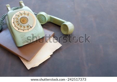 Old phone and old paper on leather background. - stock photo