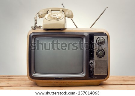 old phone and old tv vintage style on gray background . - stock photo