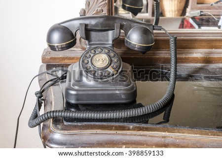 old phone dusty black Bakelite onto the shelf with a mirror background - stock photo
