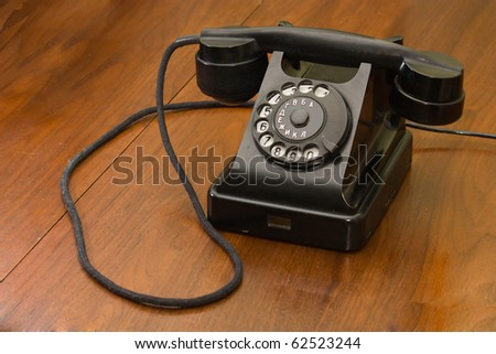 Old phone on an old wooden table - stock photo