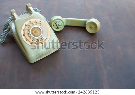 Old phone on leather background - stock photo