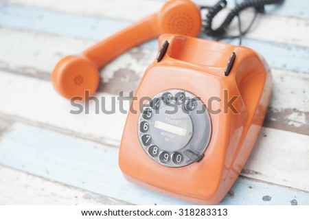 Old phone on wooden table - stock photo
