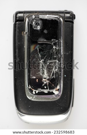 Old phone with a broken screen isolated on white  - stock photo