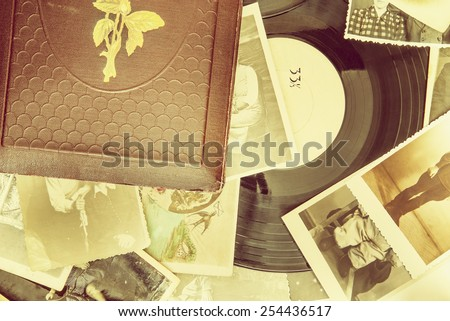 Old photo-album with retro pictures and black vinyl record on the table. - stock photo