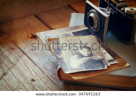 old photo camera, antique photos and old book on wooden table - stock photo