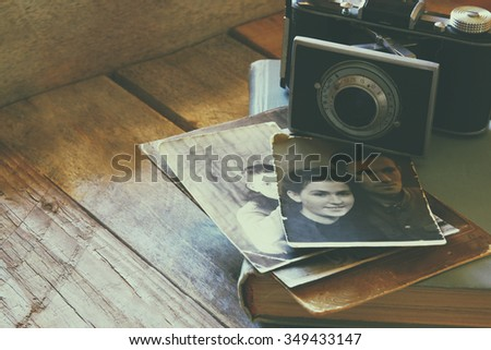 old photo camera, antique photos and old book on wooden table. faded vintage style filtered image. selective focus - stock photo