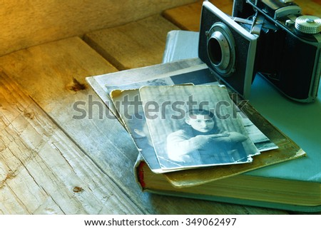 old photo camera, antique photos and old book on wooden table. retro toned and filtered image. selective focus - stock photo