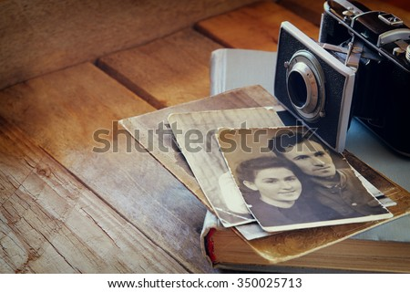 old photo camera, antique photos and old book on wooden table. vintage filtered image. selective focus  - stock photo