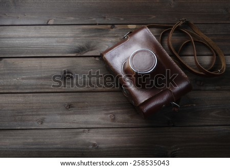 Old photo camera in leather case on wood table. - stock photo