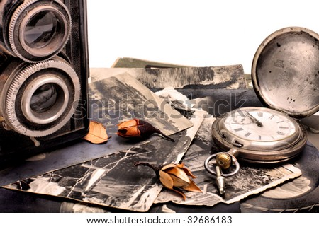 Old photo camera, old pocket watch and old photos - stock photo