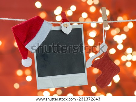 Old photo frame with Santa hat hanging on rope over red blurred background - stock photo