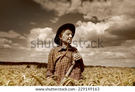 Old photo of happy senior peasant after hard work in the field - stock photo
