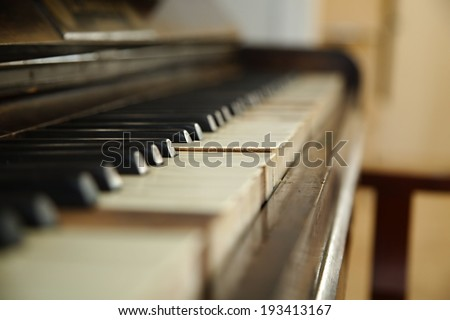 Old piano with faded keys - stock photo