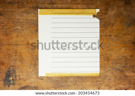 Old piece of blank scrap paper taped to an old grungy wooden board or surface. For inserting your custom message or text. - stock photo
