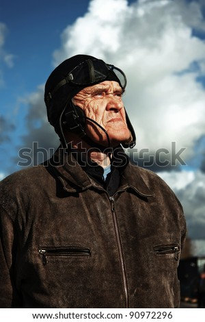 old pilot in old uniform looking upstairs to the sky - stock photo