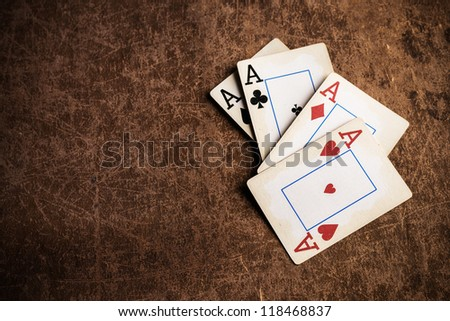 old playing cards on a brown textured background - stock photo