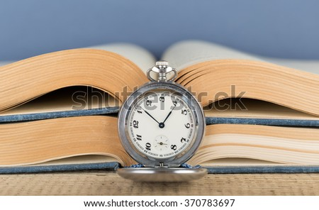 Old pocket watch and an open book - stock photo