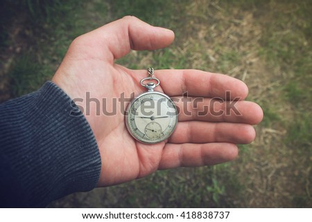 Old pocket watch in a man's hand - stock photo