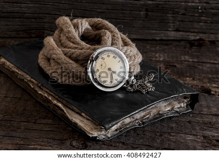 Old pocket watch on a textured vintage background - stock photo