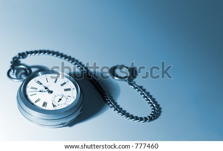 Old pocket watch with a chain, tinted blue - stock photo