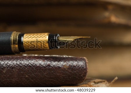 Old poetry book and a fountain pen - stock photo
