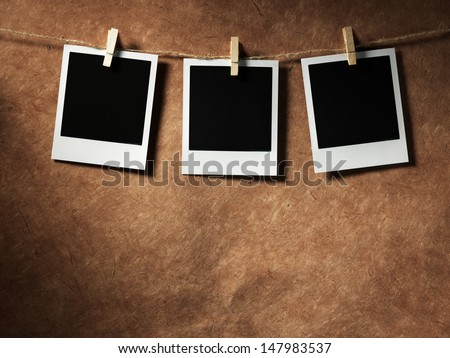 Old polaroid film blanks hanging on a rope held by clothespins. - stock photo