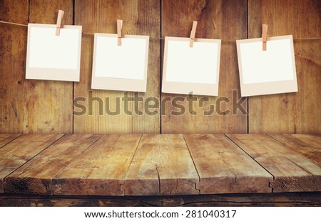 Old polaroid photo frames hanging on a rope with wooden background - stock photo