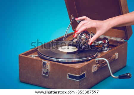 Old portable gramophone with female hand pin-up styled isolated, on blue background with empty space - stock photo