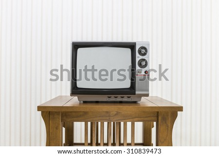 Old portable television on wood table.