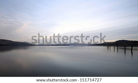 Old posts by the shores of Loch Lomond with Ben Lomond in the distance at Loch Lomond and the Trossachs National Park, Scotland - stock photo