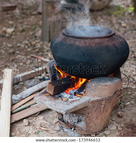 Old pot and craft for steam cooking on stove - stock photo