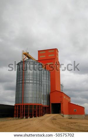 old prairie grain elevator with attached modern steel grain storage bins - stock photo