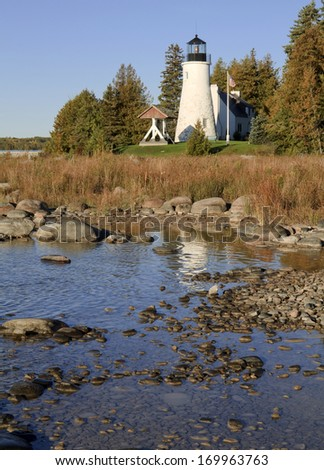 Old Presque Isle Reflection -- Old Presque isle Lighthouse reflects off the water of Lake Huron on a rocky shore. Alpena, Michigan, USA. - stock photo