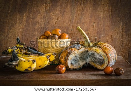 Old pumpkin,bananas and  monkey apple on table ,still life - stock photo