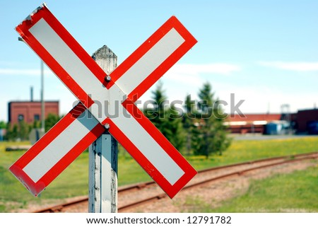 Old railroad crossing stop sign in a rural scene with shallow focus - stock photo