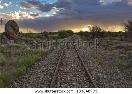 Old railway tracks in the light of setting sun and clouds before the storm and African arid landscape - stock photo