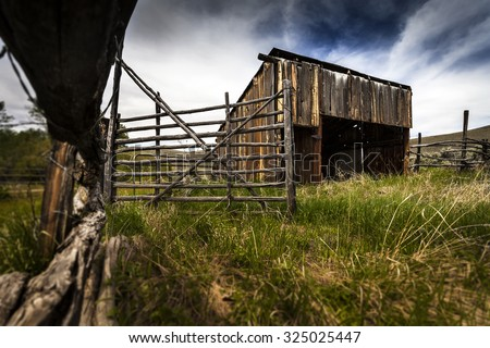 Old Ranch Stable with fencing and gate - stock photo