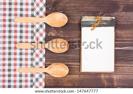 Old recipe note book, spoons, tablecloth on wood background - stock photo
