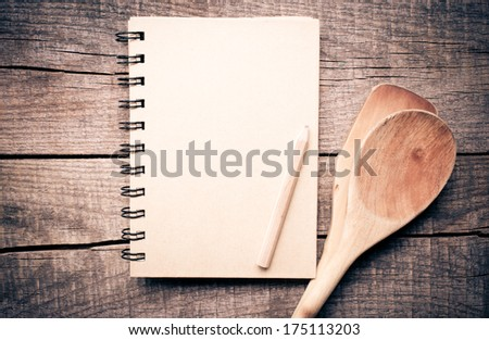 Old recipe notebook, spoons on wood background - stock photo