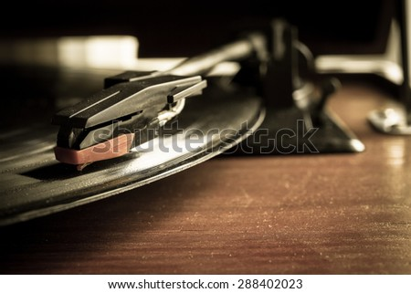 old record player stylus on a rotating disc,vintage style - stock photo