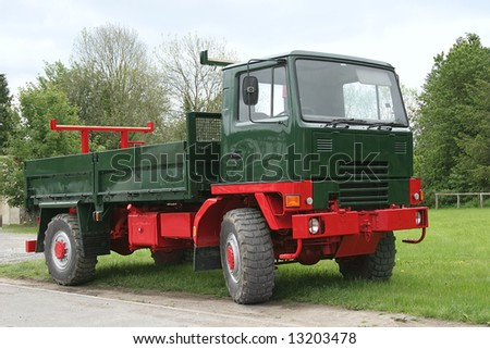 Old red and green truck with a tail gate, standing idle on the grass. - stock photo