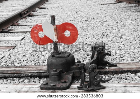 Old red and white railroad switch on tracks with gravel - stock photo