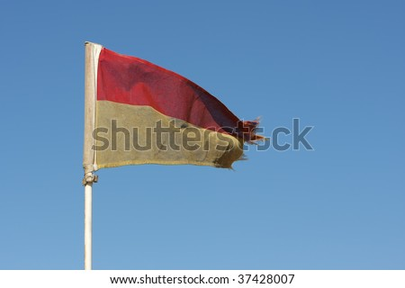 Old Red and Yellow Lifeguard flag on a South African Beach - stock photo