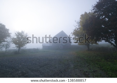 Old red barn on a blue foggy morning, Stowe, Vermont, USA - stock photo