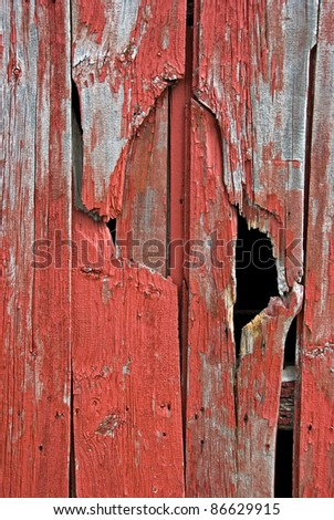 old red barn siding with hole - stock photo