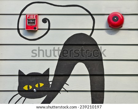 Old red box fire alarm and Red fire alarm bell on the wall with black cat painting - stock photo